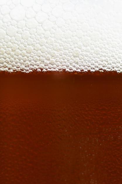 Bière. beau détail de verre battu de bière avec de la mousse. abstrait arrière-plan coloré. Photo gratuit