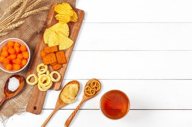 Bière blonde et des collations sur une table en bois. Photo Premium