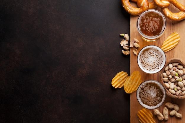 Bière blonde et des collations sur la table en pierre Photo Premium