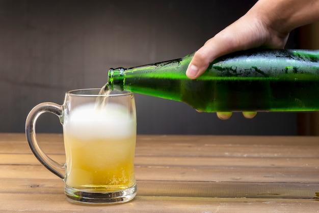 La bière coule dans un verre du mouvement de la bouteille Photo Premium