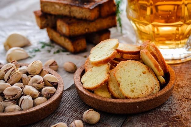Bière dans un verre, pistaches, croûtons de seigle et craquelins sur une table en bois Photo Premium