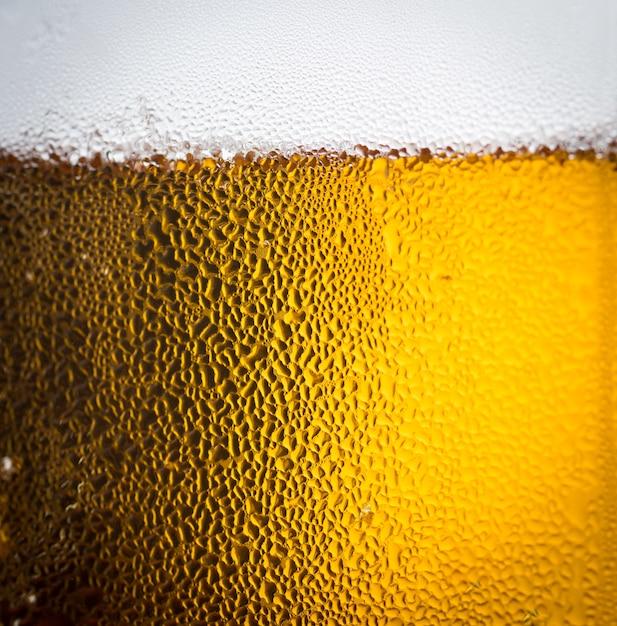 Bière de fond et des bulles avec des gouttelettes de condensation sur l'extérieur du verre Photo Premium