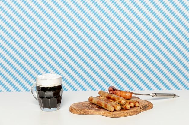 Bière noire et saucisses allemandes sur table blanche Photo gratuit