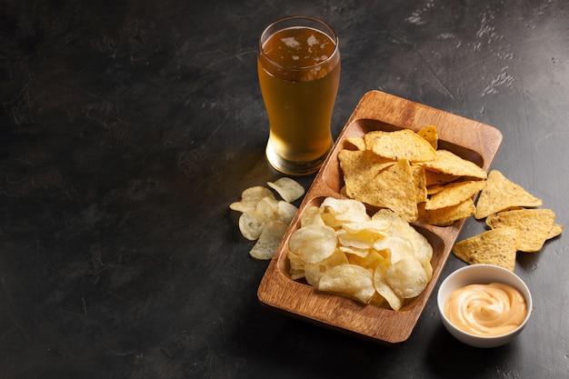 La bière avec des snacks sont des chips et des nachos. Photo Premium