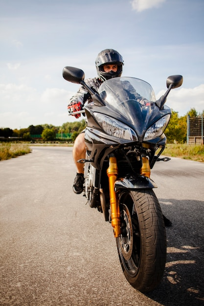 Biker à cheval sur la moto noire Photo gratuit