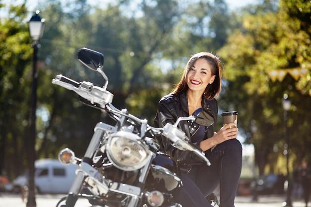 Biker girl dans une veste en cuir sur une moto Photo gratuit