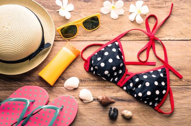 Bikini coloré de beauté et accessoires sur plancher en bois Photo Premium