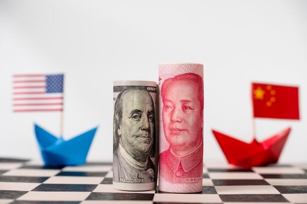 Billet de dollars américains et yuan sur l'échiquier avec les drapeaux américain et chinois. Photo Premium