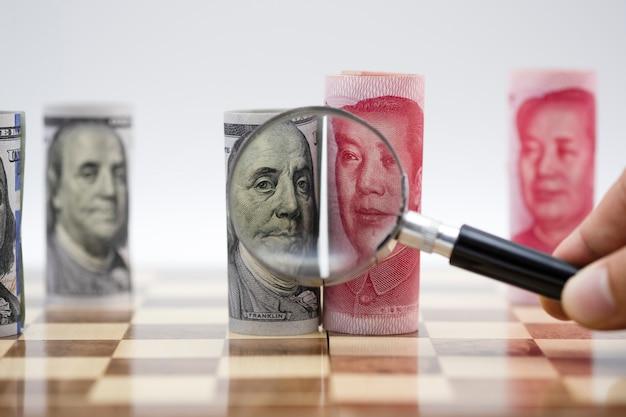 Billet en dollars américains et en yuan avec loupe sur un échiquier Photo Premium