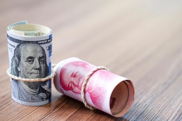 Billet en dollars américains et en yuan sur une table en bois Photo Premium