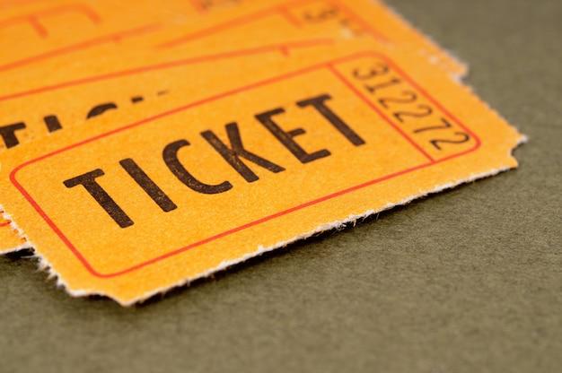 Billets d'admission orange sur fond de papier brun marbré. Photo Premium
