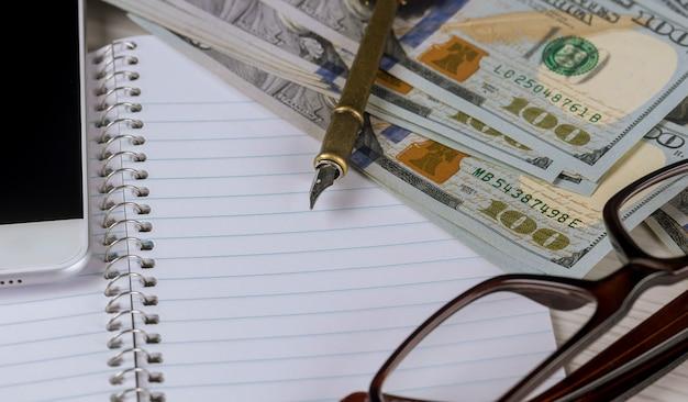 Billets de banque en dollar, gros plan se trouvent sur une feuille de papier blanc à côté d'un stylo et des lunettes dans un cadre en plastique Photo Premium