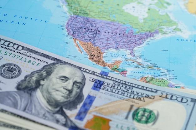 Billets de banque en dollars américains sur la carte du monde Photo Premium