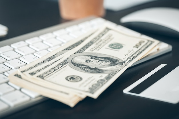 Billets de banque en dollars américains mis sur un clavier d'ordinateur de près Photo Premium