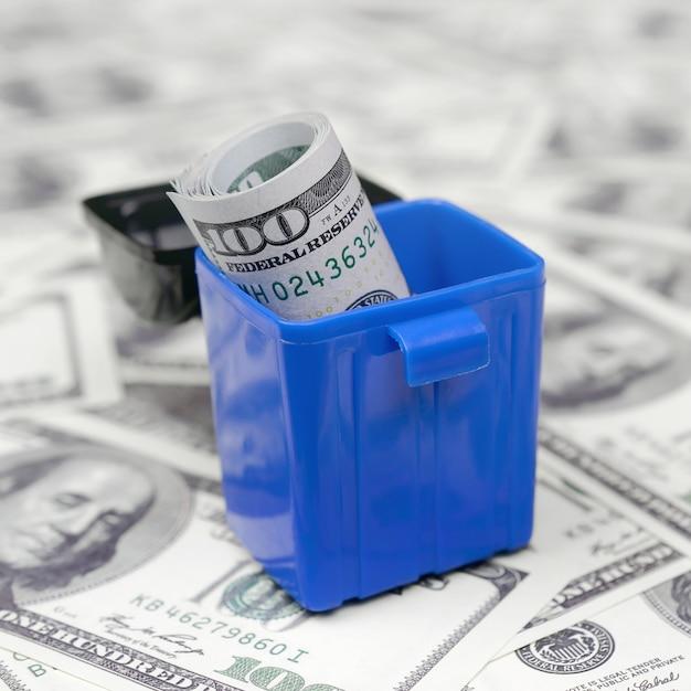 Des billets de caisse américains sont jetés à la poubelle sur une multitude de billets de cent dollars Photo Premium
