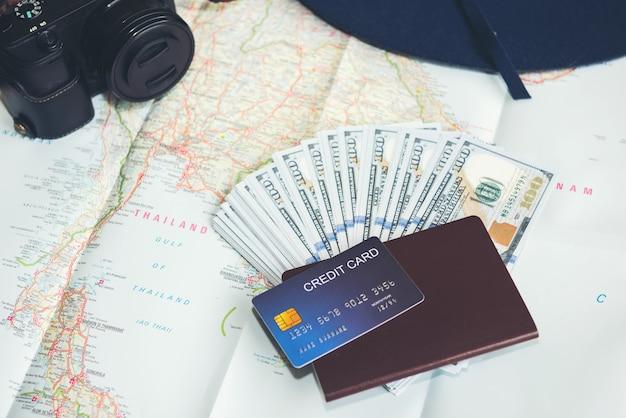 Billets de dollar, carte de crédit, passeport, appareil photo et chapeau bleu Photo gratuit