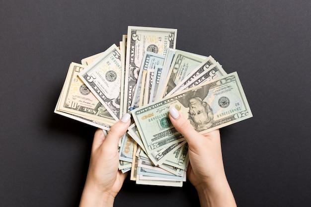 Billets de dollar différents dans des mains féminines Photo Premium