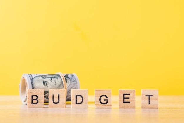 Billets d'un dollar roulés et mot budget. concept de comptabilité financière Photo Premium