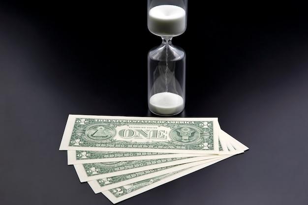 Les Billets D'un Dollar Se Trouvent Près Du Sablier. Le Temps, C'est De L'argent. Le Salaire. Solutions D'affaires Dans Le Temps. Mesure Du Temps De Sablier Photo Premium
