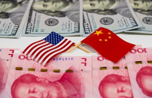 Billets de dollar des usa et billets de chine yuan avec à travers le drapeau de l'amérique et le drapeau de la chine Photo Premium