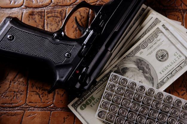 Billets en dollars et armes à feu, pistolet noir Photo Premium