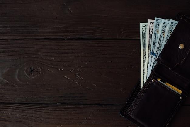 Billets en dollars dans le portefeuille des hommes en cuir sur une table en bois marron Photo gratuit