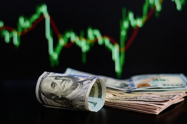 Billets de dollars en rouleaux sur fond de cotes boursières. finance et un concept d'entreprise Photo Premium