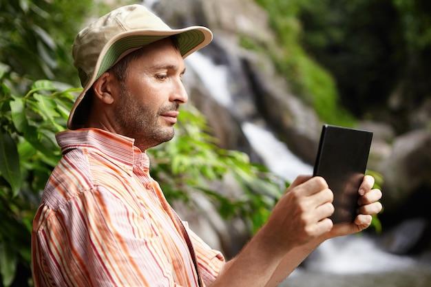 Biologiste Masculin En Chemise Rayée Et Chapeau Travaillant Dans Un Parc Naturel, Prenant Des Photos Ou Enregistrant Une Vidéo De La Faune à L'aide De Sa Tablette Numérique Noire Debout Contre La Cascade Et Les Arbres Verts Photo gratuit