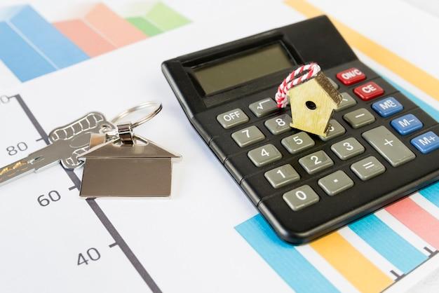 Birdhouse minuscule sur la calculatrice et porte-clés de maison sur le graphique Photo gratuit
