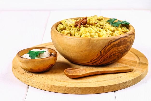 Biryani indien avec poulet, yaourt, assiette d'épices sur une table en bois. nouvel an, plat de noël. Photo Premium