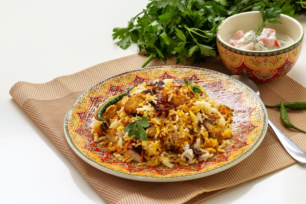 Biryani de poulet indien halal servi avec raita de tomates au yaourt Photo Premium