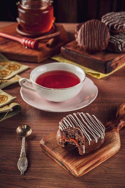 Un Biscuit Au Miel Brésilien Mordu Au Chocolat Recouvert Sur La Table En Bois Avec Une Tasse De Thé En Porcelaine, Miel Et Cannelle - Pao De Mel Photo Premium