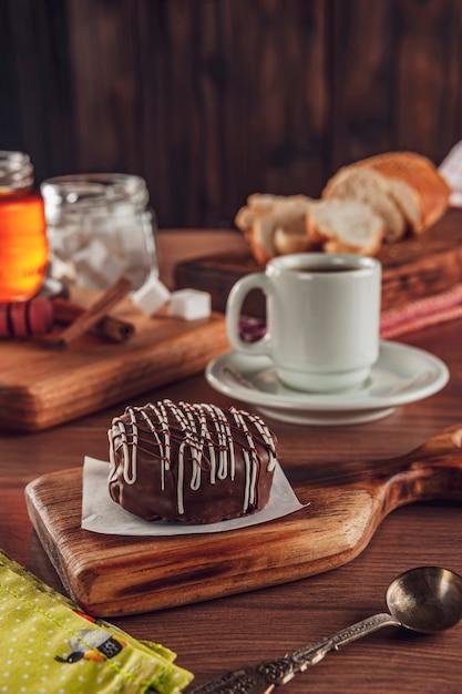 Biscuit Au Miel Brésilien Recouvert De Chocolat Sur La Table En Bois Avec Café - Pao De Mel Photo Premium