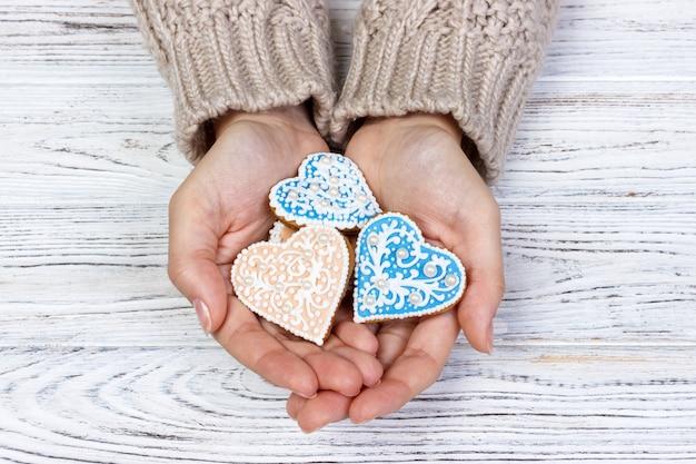 Biscuit en forme de coeur dans les mains de la femme Photo Premium