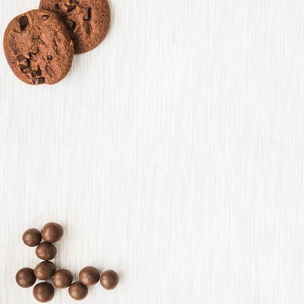 Biscuits au chocolat et boule sur fond de texture en bois Photo gratuit