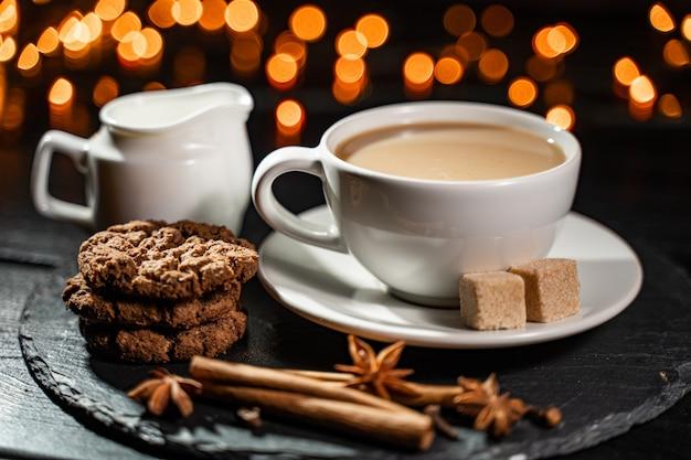 Biscuits Au Chocolat, Café, épices Sur Les Lumières De Noël Floues. Photo Premium