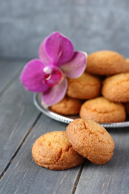 Biscuits aux amandes avec fleur d'orchidée sur une table en bois rustique Photo Premium