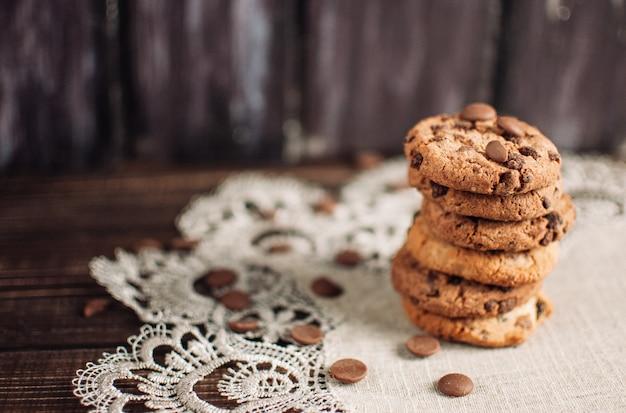 Biscuits aux pépites de chocolat empilés sur une toile de lin Photo Premium