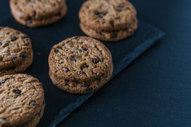 Biscuits aux pépites de chocolat à la main sur une table de tableau. Photo Premium