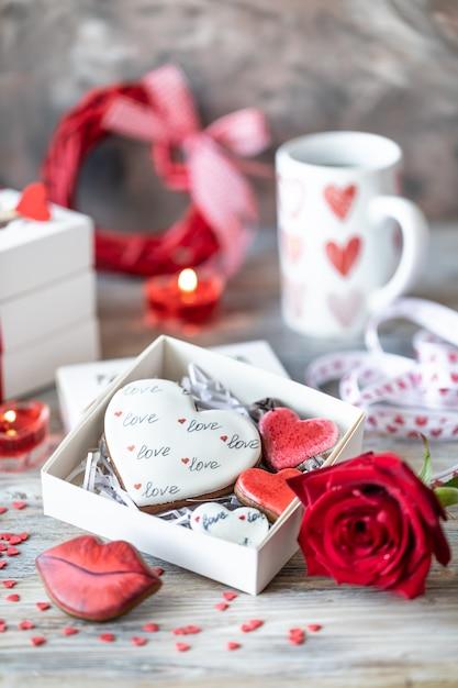 Biscuits Ou Biscuits De Pain D'épice Dans Une Boîte Cadeau Avec Un Ruban Rouge Sur Une Table En Bois. La Saint-valentin. Photo Premium