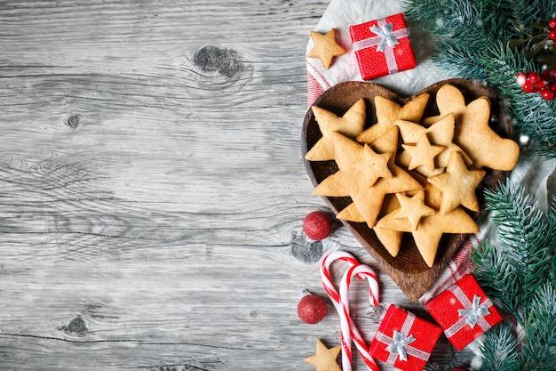 Biscuits cadeaux et des branches de sapin sur une table en bois. Photo Premium