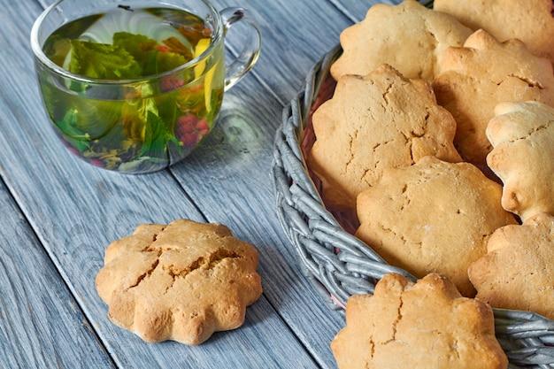 Biscuits dans le panier en osier de tubes de journal et une tasse de thé vert transparente Photo Premium