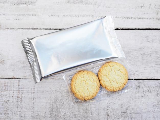 Biscuits et emballage en aluminium sur fond de bois Photo Premium