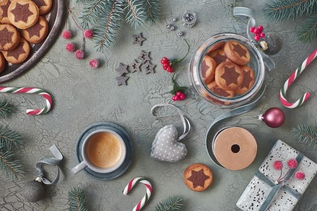 Biscuits étoiles de noël sur fond vert rustique avec des brindilles de sapin et des décorations de noël Photo Premium