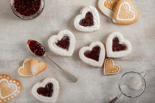 Biscuits Faits Maison Avec De La Confiture De Framboises Sur Une Table En Bois Blanche Pour Noël Ou La Saint-valentin. Photo Premium
