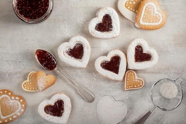 Biscuits En Forme De Coeur Faits Maison Avec De La Confiture De Framboises Sur Une Table En Bois Blanc Pour Noël Ou La Saint-valentin. Vue De Dessus. Photo Premium