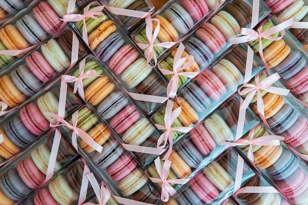 Biscuits Macaroni De Différentes Couleurs Dans Un Emballage Avec Un Arc, Beaucoup De Boîtes Avec Des Cookies Sous Forme De Texture. Photo Premium