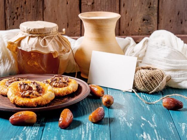 Biscuits, miel, dates, pot à lait et carte sur bois turquoise Photo Premium