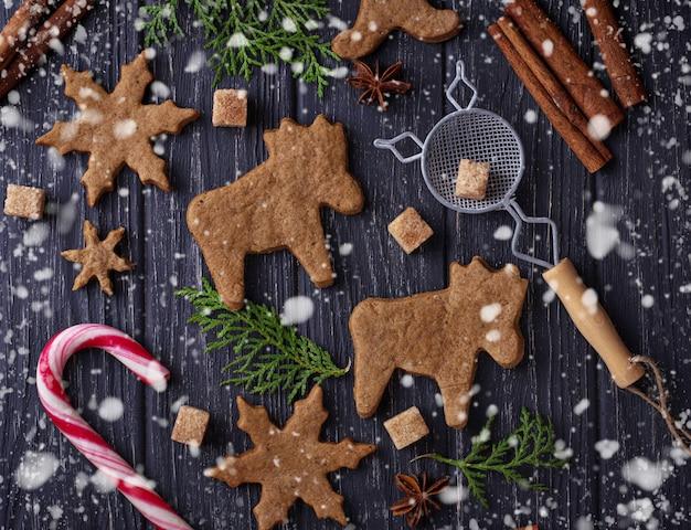 Biscuits de noël en forme de cerf et de flocon de neige. mise au point sélective, effet de neige Photo Premium