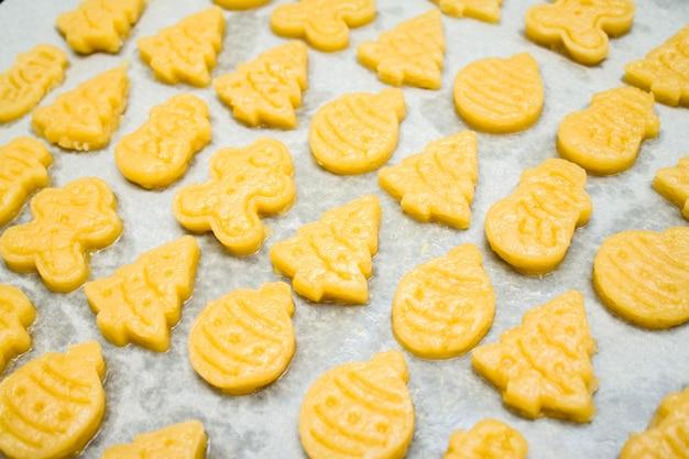 Biscuits de noël en pâte de pain d'épice pour enfants en forme de boule, sapin, bonhomme de neige Photo Premium